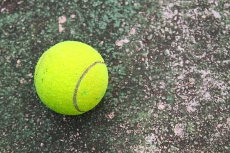 old tennis ball on grunge dirty floor photo