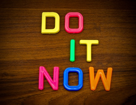 Do it now in colorful toy letters on wood background photo