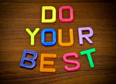 Do your best in colorful toy letters on wood background photo