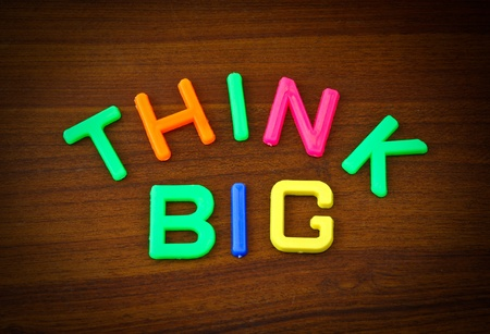 Think big in colorful toy letters on wood background photo