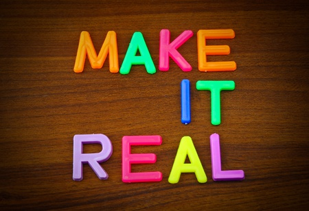 Make it real in colorful toy letters on wood background photo