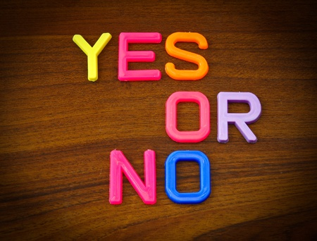 Yes or no in colorful toy letters on wood background photo