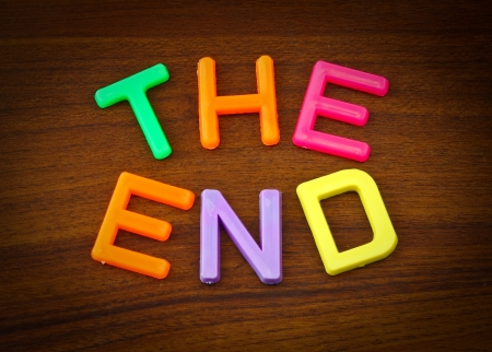 The end in colorful toy letters on wood background photo