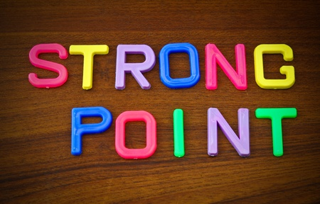 Strong point in colorful toy letters on wood background photo