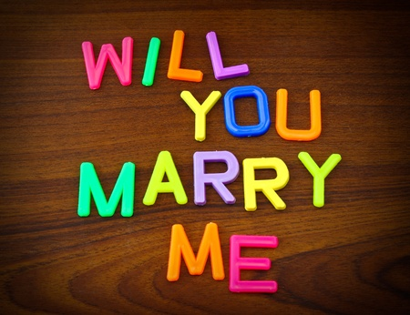 Will you marry me in colorful toy letters on wood background photo