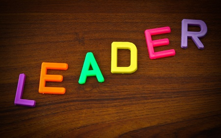 Leader in colorful toy letters on wood background photo