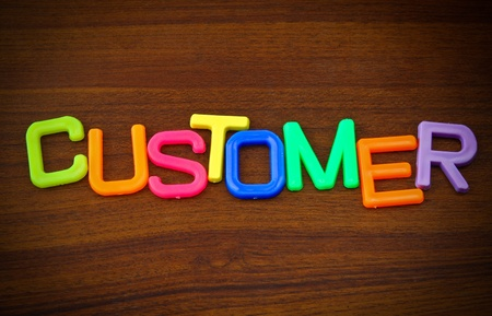 Customer in colorful toy letters on wood background photo