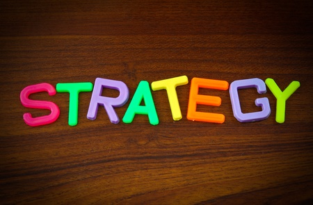 Strategy in colorful toy letters on wood background photo