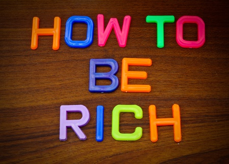 How to be rich in colorful toy letters on wood background Stock Photo - 10563627