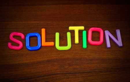 Solution in colorful toy letters on wood background Stock Photo - 10563625