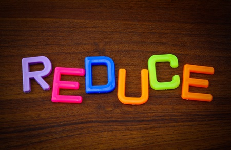 Reduce in colorful toy letters on wood background Stock Photo - 10563610