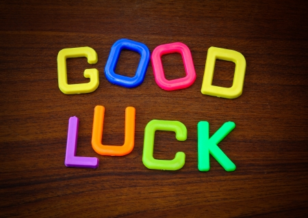 Good luck in colorful toy letters on wood background photo