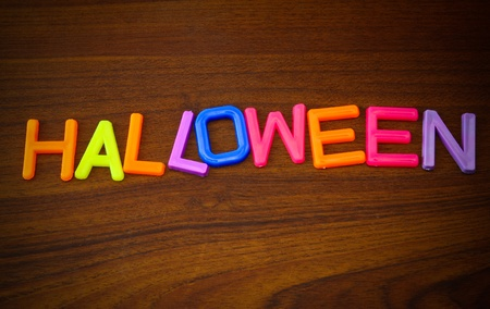 Halloween in colorful toy letters on wood background  photo