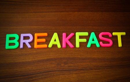 ฺBreakfast in colorful toy letters on wood background  photo