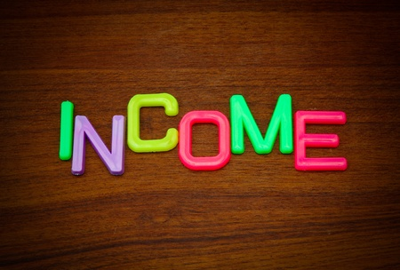 Income in colorful toy letters on wood background  photo