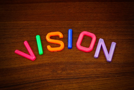 Vision in colorful toy letters on wood background  Stock Photo - 10575384