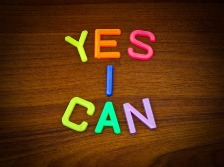 willing: Yes I can in colorful toy letters on wood background Stock Photo