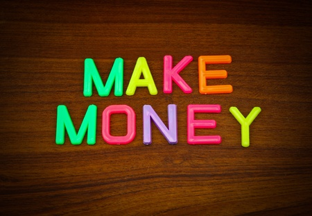 Make money in colorful toy letters on wood background photo