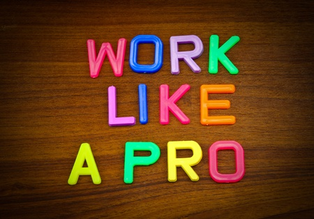 Work like a pro in colorful toy letters on wood background photo