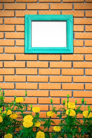 Vintage picture frame on brick wall with yellow flower photo