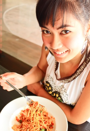 woman eating spaghetti in restaurant photo