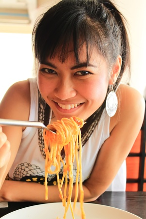 Beautiful asian woman eating spaghetti in restaurant  photo