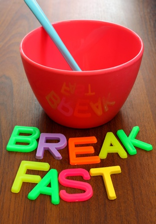 soup spoon: blue spoon in pink bowl with breakfast in colorful letters on wood background