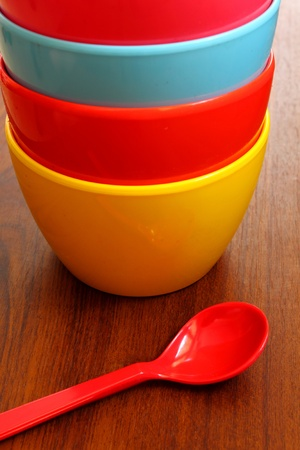 Stack of colorful plastic bowl with blue spoon photo