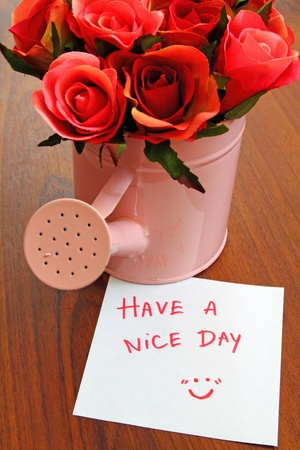 writing message have a nice day with bouquet roses in watering can  photo
