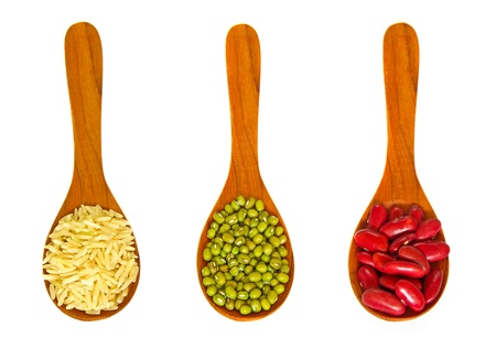 Rice and beans in wooden spoons on white background photo