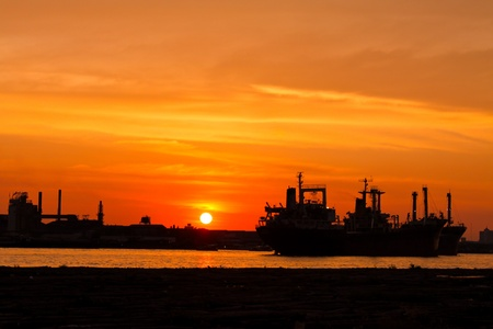 a big ship: industrial ship and factory silhouetted at sunset with river Stock Photo