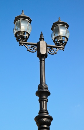 Old vintage street light against blue sky photo