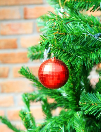 Christmas tree with red ball and brick wall photo