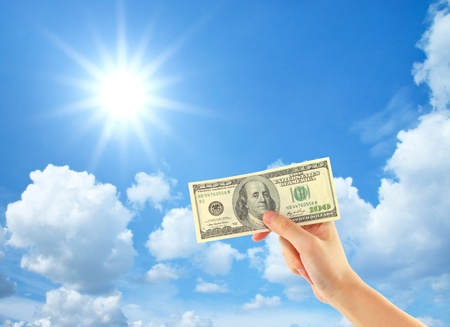 Hand showing money over sky with clouds and sun photo