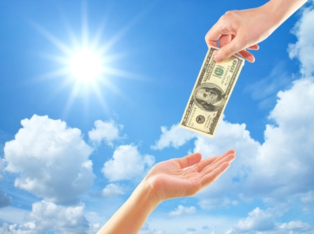 Hand giving money to other hand over clouds and sun photo