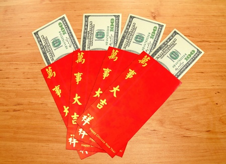 Money Dollar Cash Banknote in Red Envelope on Wood Background photo