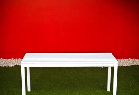 white bench with red wall photo