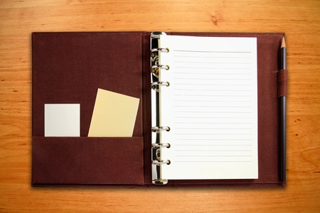 Brown canvas binder notebook with blank card and pencil on wooden background photo