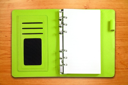 Green leather binder notebook on wooden background photo