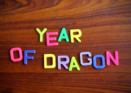 Year of dragon in colorful toy letters on wood background photo