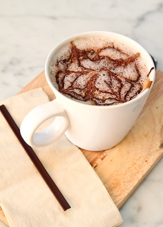 Hot chocolate with syrup on chopping board photo