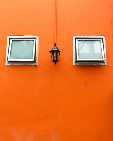 old lamp with windows on orange wall photo