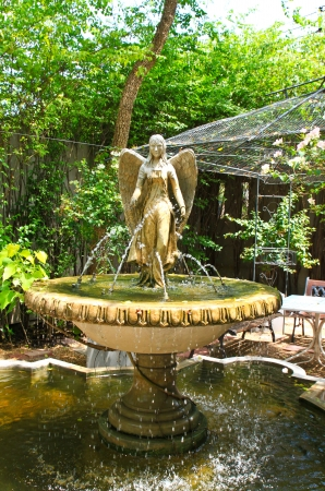 Angel sculpture fountain in the garden photo