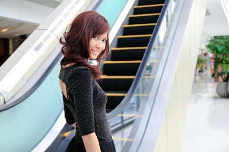 an escalator: Young asian woman on elevator looking back