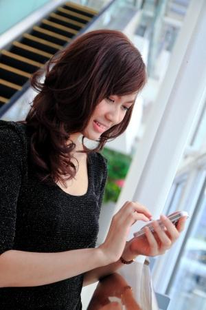 Mujer de negocios de Asia con un teléfono celular