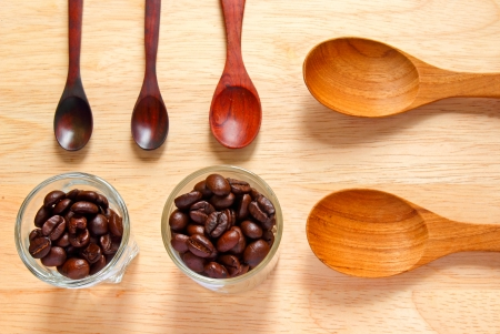Collection of wooden kitchen spoons with coffee beans on wood background photo