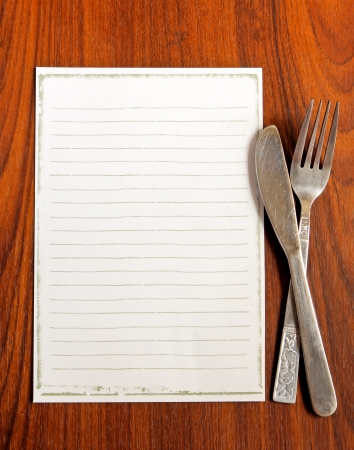 meny: papper för menyn med kniv och gaffel på trä bakgrund Stockfoto