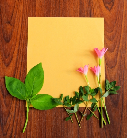 Flowers and leaves with yellow paper on wooden background photo
