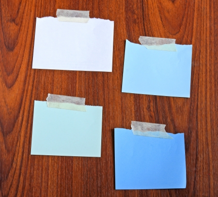 Notepaper attach with tape on wooden background photo