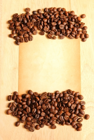 Coffee beans with old paper for notes on the wooden background photo